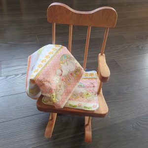 Rocking chair with cushion and matching doll blanket.