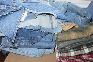 Stack of jeans, flannel pjs and flannel scraps - partially cut.