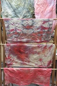 Some of the rinsed fabric drying on a rack